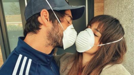 Isco dan pasangannya berbagi ciuman meski menggunakan masker di tengah penyebaran virus Corona. - INDOSPORT