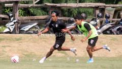 Indosport - Pemain PSS Sleman Irkham Mila (kanan) berebut bola dengan Samsul Arifin dalam latihan di Lapangan Yogyakarta Independent School (YIS).