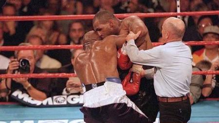 Aksi gigitan Mike Tyson ke telinga Evander Holyfield pada ronde ketiga, dalam pertarungan tinju kelas berat, (28/06/1997). - INDOSPORT