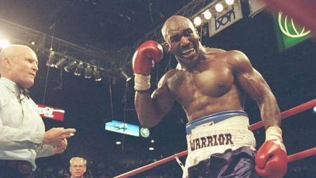 Saat Evander Holyfield menunjuk ke telinganya yang berdarah setelah Tyson menggigitnya pada ronde ketiga gelar kelas berat mereka di MGM Grand Garden di Las Vegas, Nevada (28/06/1997). - INDOSPORT