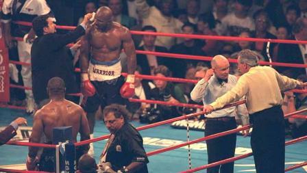 Wasit Mills Lane menunjukkan ke telinga Evander Holyfield yang berdarah setelah Tyson menggigitnya di babak ketiga.
