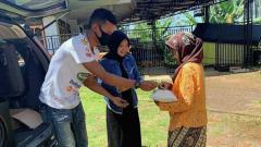 Indosport - Bek Badak Lampung, Ikhfanul Alam (kiri) saat membagikan bantuan dari hasil lelang Jersey, kepada sejumlah masyarakat di kabupaten Malang.