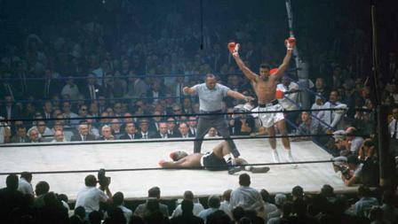 Petinju kelas berat Muhammad Ali mengangkat kedua tangan usai meng-KO Sonny Liston pada ronde pertama di Arena St. Dominic (25/05/1995). Kala itu, duel ini disinyalir adalah match fixing lantaran Sonny terlalu mudah menyerah dengan pukulan lemah.