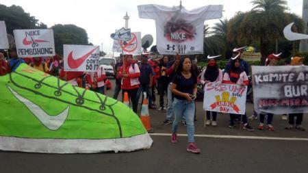 Para buruh sepatu Nike menyampaikan tuntutannya pada Hari Buruh. - INDOSPORT