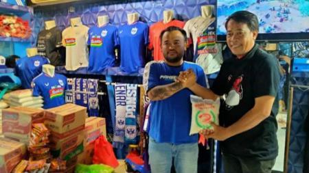 Ketum Panser Biru, Kepareng (kiri) menerima amanah untuk menyalurkan sembako dari perwakilan The Jakmania Semarang - INDOSPORT