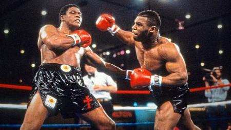 Trevor Berbick (kiri) menerima hantaman hook dari Mike Tyson muda di tahun 1986. - INDOSPORT