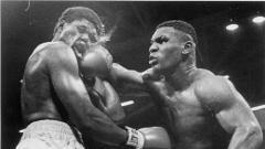 Indosport - James Tillis (kiri) menerima pukulan keras dari Mike Tyson dalam laga tinju kelas berat tahun 1986.