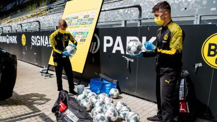 Bola untuk laga Borussia Dortmund vs Schalke 04 disemprot disinfektan.