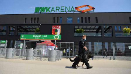 Seorang polisi dan anjing penjaga berpatroli di luar WWK-Arena dalam laga Bundesliga antara FC Augsburg vs VFL Wolfsburg, Sabtu (16/05/20).