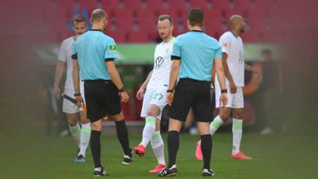 Maximilian Arnold, pemain Vfl Wolfsburg beradu sepatu dengan asisten wasit setelah laga Bundesliga antara FC Augsburg vs VFL Wolfsburg, Sabtu (16/05/20).