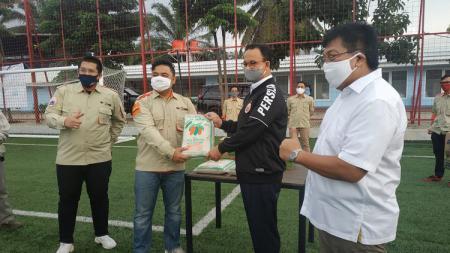 Mantan Direktur Utama Persija Jakarta, Gede Widiade, menyerahkan bantuan secara simbolis kepada Gubernur DKI Jakarta, Anies Baswedan. - INDOSPORT