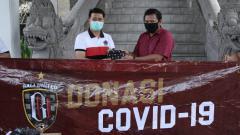 Indosport - Bupati Klungkung, I Nyoman Suwirta (kiri) menerima penyerahan masker dari Bali United yang diwakili general secretary, Michael Gerald (kanan). Foto : Bali United