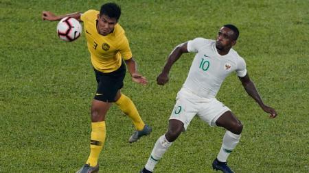 Greg Nwokolo (kanan) striker Timnas Indonesia saat berduel dengan pemain Malaysia di ajang kualifikasi Piala Dunia 2022 - INDOSPORT