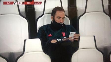 Higuain tertangkap kamera bermain HP di semifinal Coppa Italia antara Juventus vs AC Milan. - INDOSPORT