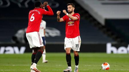Paul Pogba dan Bruno Fernandes merayakan gol dalam pertandingan Liga Inggris Tottenham Hotspur vs Manchester United, Sabtu (20/06/20). - INDOSPORT