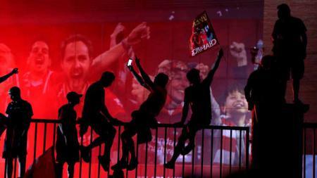 Fan Liverpool merayakan di luar Anfield, Liverpool. - INDOSPORT