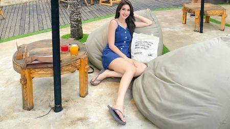 Aktris sekaligus penyanyi kondang, Elma Agustin, menunjukkan body goalsnya saat bersiap surfing atau berselancar di Jimbaran, Bali. - INDOSPORT