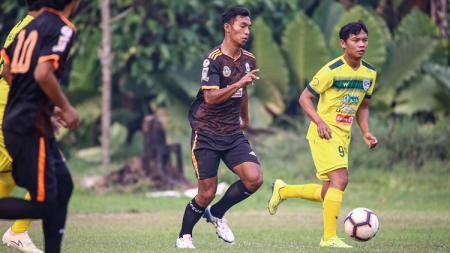 Pemain muda PSIS Semarang, Andreas Chrismanto Ado (kaos hitam) saat membawa bola dan dibayangi M. Nasuha (kaos kuning). - INDOSPORT
