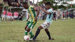 Indosport - Pemain klub Liga 2 Sulut United, Ilham Fathoni (biru), mengawal pemain PSBS Biak