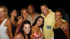 Indosport - Mike Tyson (tengah) saat menghadiri sebuah pesta bersama beberapa rekan wanitanya.