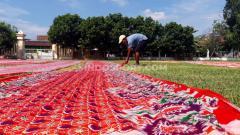Indosport - Seorang warga melakukan aktifitas menjemur kain batik usahanya di salah satu lapangan pendamping Stadion Manahan untuk Piala Dunia U-20 2021, yakni Lapangan Sriwaru di Kampung Sondakan.