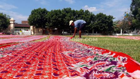 Seorang warga melakukan aktifitas menjemur kain batik usahanya di salah satu lapangan pendamping Stadion Manahan untuk Piala Dunia U-20 2021, yakni Lapangan Sriwaru di Kampung Sondakan.