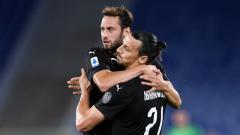 Indosport - Selebrasi Hakan Calhanoglu dan Zlatan Ibrahimovic dalam laga Lazio vs AC Milan di Liga Italia 2019-20, Minggu (05/07/20).