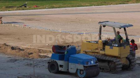 Alat berat terlihat untuk meratakan tanah lapangan di Stadion Gelora 10 November. - INDOSPORT