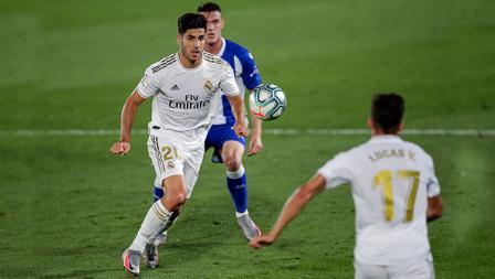 Bintang Real Madrid Marco Asensio, menggiring bola ke area pertahanan Deportivo Alaves.