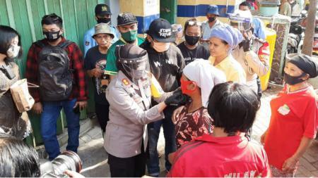 Suporter Persebaya Surabaya, bonek tribune timur membagikan masker di pasar pabean dan pasar kilometer. - INDOSPORT