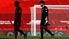 Indosport - Virgil van Dijk dan Alisson Becker tertunduk lesu usai melakukan blunder di laga Arsenal vs Liverpool
