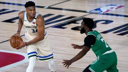 Giannis Antetokounmpo, pemain Milwaukee Bucks diadang Jaylen Brown dari Boston Celtics dalam laga NBA di Florida, Sabtu (01/08/20).