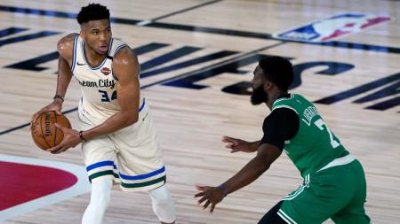 Giannis Antetokounmpo, pemain Milwaukee Bucks diadang Jaylen Brown dari Boston Celtics dalam laga NBA di Florida, Sabtu (01/08/20). - INDOSPORT