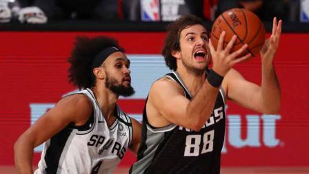 Nemanja Bjelica (Sacramento Kings) dilanggar pemain San Antonio Spurs, Derrick White dalam laga NBA di ESPN Wide World Of Sports Complex, Sabtu (01/08/20).
