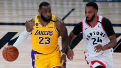 Indosport - LeBron James (LA Lakers) berjibaku dengan Norman Powell (Toronto Raptors) di laga NBA yang berlangsung di  ESPN Wide World Of Sports Complex, Minggu (02/08/20).