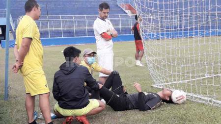 Kurniawan Kartika Ajie mendapat perawatan usai mendapat cedera saat latihan perdana Arema FC di Stadion Kanjuruhan, Senin (03/08/20). - INDOSPORT