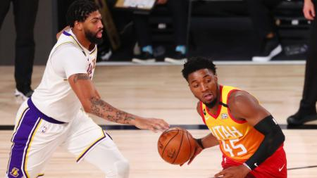 Donovan Mitchell (Utah Jazz) mengontrol bola melewati Anthony Davis (Los Angeles Lakers) di laga NBA, ESPN Wide World Of Sports Complex Florida, Selasa (04/08/20). - INDOSPORT