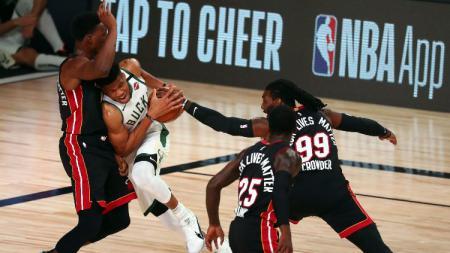 Pemain Milwaukee Bucks Giannis Antetokounmpo diadang Bam Adebayo dan pemain Miami Heat lainnya di laga NBA, Jumat (07/08/20). - INDOSPORT