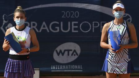 Simona Halep dan Elise Mertens berfoto di podium juara Praha Terbuka dengan menerapkan physical distancing.