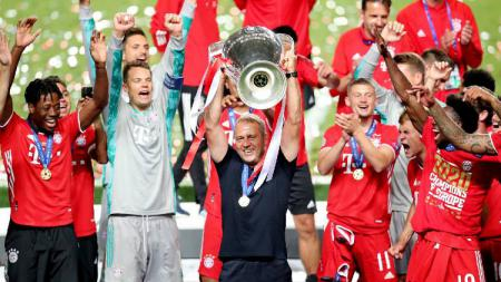 Pelatih Bayern Munchen, Hansi Flick, mengangkat trofi Liga Champions. - INDOSPORT