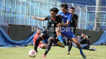 Jayus Hariono berebut bola dengan pemain Kaki Mas Dampit dlm uji coba Arema FC - INDOSPORT