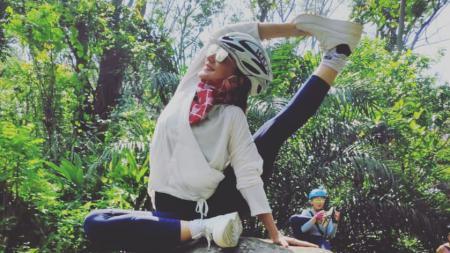 Wanda Hamidah stretching di atas batu - INDOSPORT