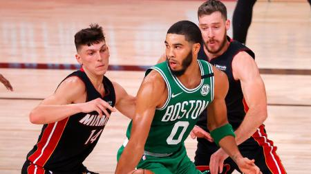 Jayson Tatum (Boston Celtics) diadang dua pemain Miami Heat di playoffs NBA, Minggu (20/09/20). - INDOSPORT