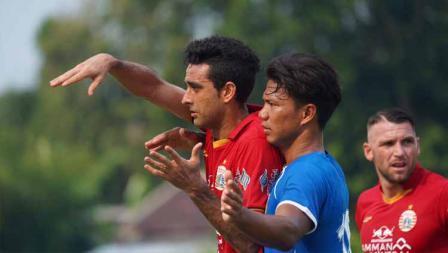 Bek Bhayangkara FC, Achmad Jufriyanto (tengah) menjaga ketat striker Persija, Marko Simic pada uji coba antara Persija vs Bhayangkara, Rabu (22/09/20).