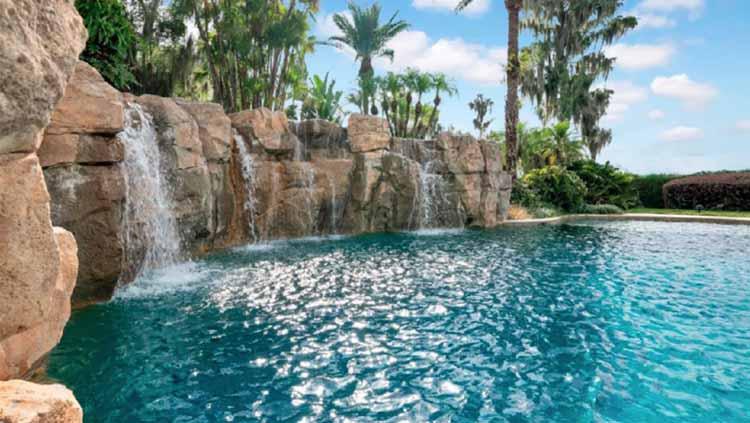 Air terjun besar jatuh ke kolam renang yang dikelilingi oleh pohon palem. Copyright: ATLAS TEAM/COMPASS