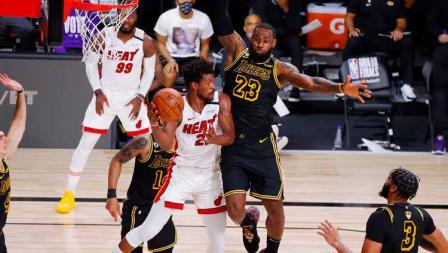 LeBron James berusaha menghalangi Jimmy Butler yang ingin mencetak poin di laga final NBA 2019/20 antara LA Lakers vs Miami Heat.