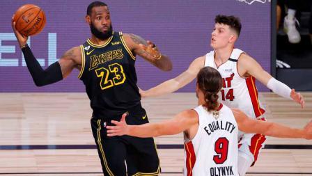 Dua pemain Miami Heat menempel ketat LeBron James yang hendak mengoper bola ke rekan-rekannya di LA Lakers.
