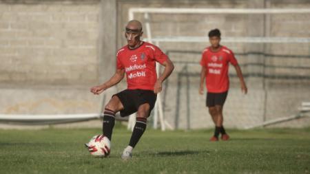 Pemain Bali United M Sidik Saimima menggunakan pelindung wajah dalam sesi latihan. - INDOSPORT