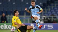 Indosport - Ciro Immobile saat berduel dengan Mats Hummeles di laga Lazio vs Borussia Dortmund