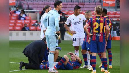 Lionel Messi menerima perawatan medis saat mengalami cedera dalam pertandingan antara Barcelona vs Real Madrid di Camp Nou, Sabtu (24/10/2020).